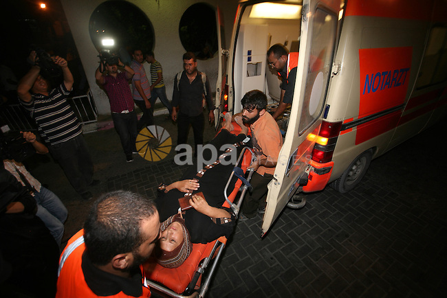 Palestinians wheel a wounded woman following an Israeli attack in Gaza City on August 19, 2011.  Photo by Mahmud Nassar