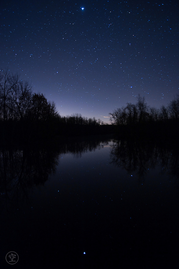 Blue night on the Beaver River, with stars reflecting in the water.