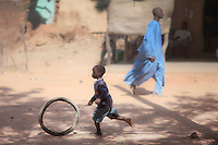 A boy running in the street uses an old tire as a toy, Markala, Mali.