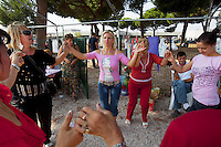 Italy. Lazio region. Rome. Anagnina park. On sunday afternoon, the romanian women, all immigrants, meet there, dance and spend time together. A woman wears a pink t-shirt with an image of a woman's naked back and the words: I lost my shirt on the Dodgers. Another has a leopard drawing on her chest. Romanian immigration. Anagnina is the south-eastern terminus of Line A of the Rome Metro. It is located at the junction of the Via Tuscolana and the Via Anagnina, close to the depot of Osteria del Curato. 25.09.2011 © 2011 Didier Ruef