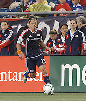 New England Revolution midfielder Ryan Guy (13) brings the ball forward.  In a Major League Soccer (MLS) match, Real Salt Lake (white)defeated the New England Revolution (blue), 2-1, at Gillette Stadium on May 8, 2013.