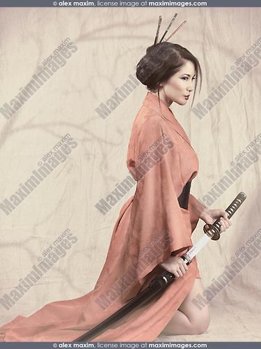 Beautiful asian woman in red kimono kneeling with an unsheathed katana sword. Vintage stylized photo.