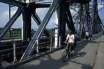 Heavily damaged during the Vietnamese war by American planes and repaired, the Paul Doumer Bridge's outer spans are now used only for foot and bicycle traffic in Hanoi, North Vietnam.  (Jim Bryant Photo).....
