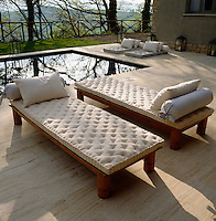 Teak sun-loungers on the swimming pool terrace are covered in a comfortable mattress and dressed with bolsters and cushions