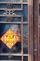 A dirty window of a porcelain shop in Shichahai area of Beijing,China hangs a luck sign from the Spring Festival.