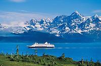 Holland America cruise boat passes through Port Wells in Prince William Sound, Alaska. Chugach mountains in the distance.