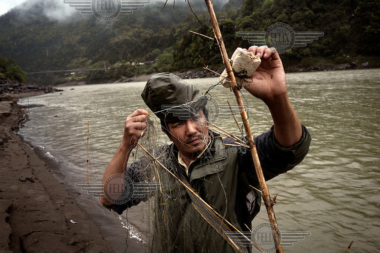 Li Zheng Xin, 36, a farmer who goes fishing whenever he can, sets a net to catch fish in the Nujiamg River in Chala Village.