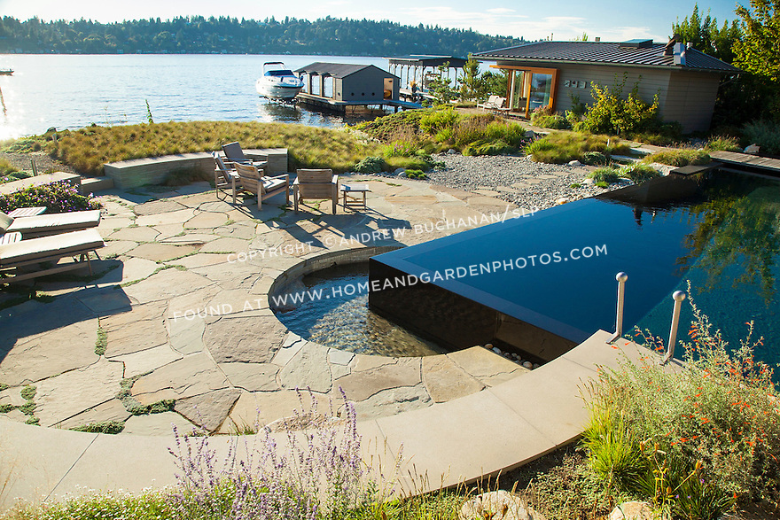 A circular spa sits tucked at the corner of the rectangular infinity pool in the beautiful, Kandinsky-inspired yard of a waterfront home.