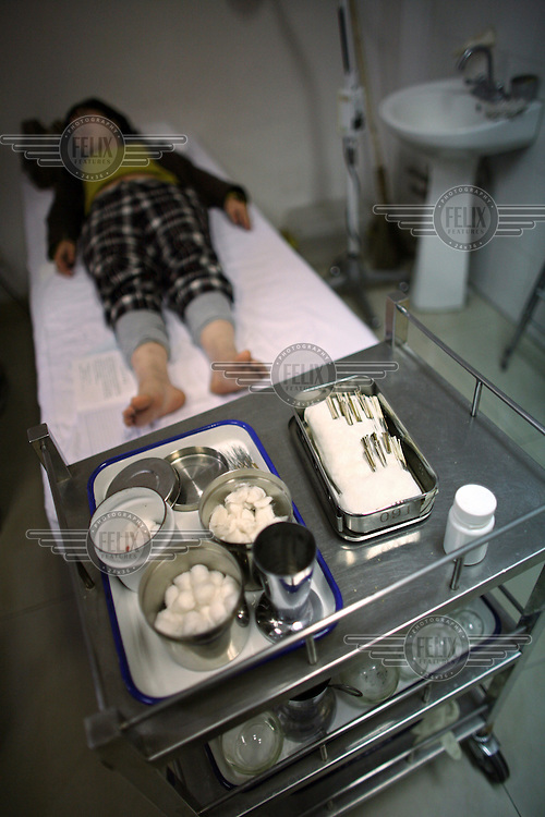 An woman lies on a bed in an examination room before receiving accupuncture treatment at a Beijing hospital.  The medical equipment of cotton wool and acupuncture needles are laid out on a tolley at the end of the bed..