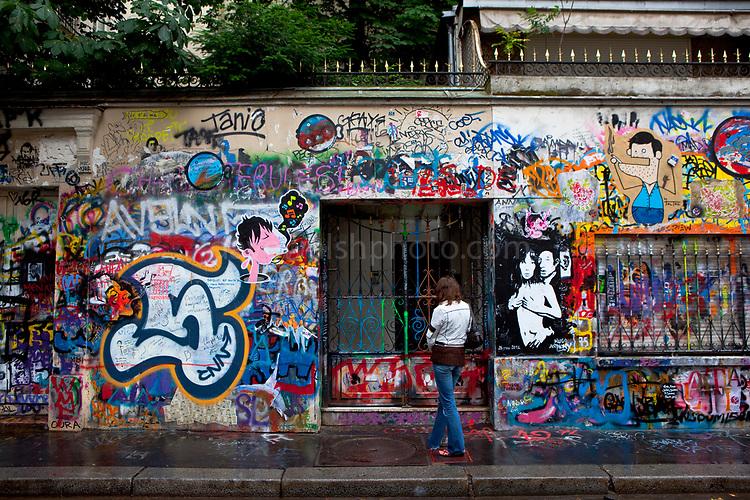 A woman pauses outside the house of Serge Gainsbourg, 5 Bis Rue de Verneuil, 75006 Paris, France.  La maison de Serge Gainsbourg.