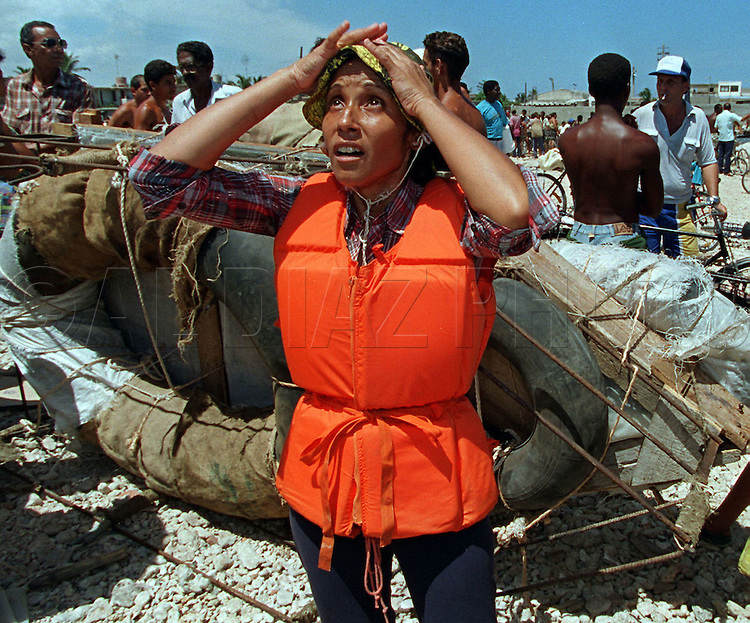 8/1994-Al Diaz/Miami Herald--In 1994 Cuban balseros turned the tiny fishing village of Cojimar into a major point of embarkation for thousands seeking a better life. Here, Gladys Garces, 42, prays for a safe journey to South Florida before boarding a raft in Cojimar.
