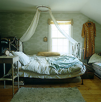 In this bedroom an old-fashioned wrought-iron bed has been placed next to the window with an antique settle at its foot