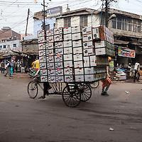 Agra, India.  Street Scene, Kinari Bazaar Area.  Three-wheeled Cart Moving Boxes of Running Shoes.