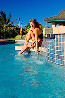 Woman Sitting By Waterfall Pool