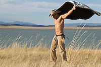 shirtless cowboy holding a blanket in the wind by a lake in New Mexico