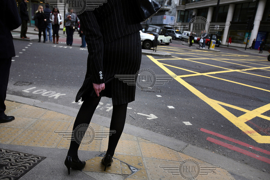 Workers employed in the City of London wait to cross a road. The UK went into recession in the final quarter of 2008 as the City was hit hard by the global credit crunch.