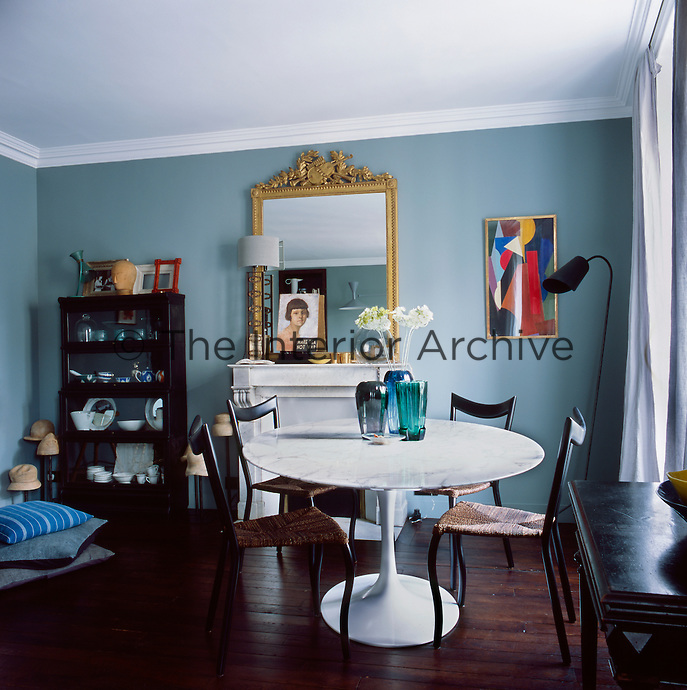 The informal dining room has blue grey walls, a wood floor and a marble fireplace. The room is furnished in an eclectic mix of styles