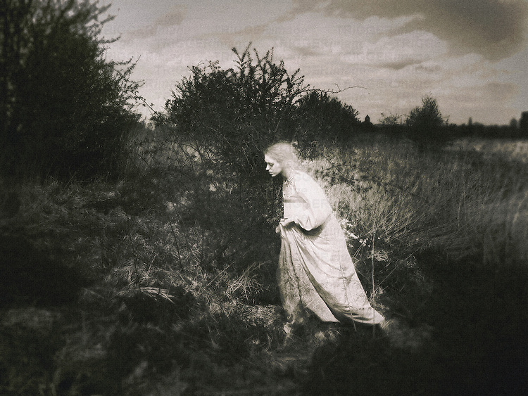 A woman in white outfit, with a pale complexion and hair, and a book under her left hand, walking among the trees in a garden/field.