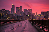 Minneapolis skyline with a colorful sunset from the Stone Arch Bridge as a rain storm breaks.