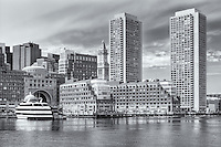 Part of the waterfront skyline including the Boston Harbor Hotel at Rowes Wharf and the Harbor Towers condos in Boston, Massachusetts.  The Odyssey Cruises cruise ship is docked at the wharf and the historic Custom House Tower can be seen in the background.