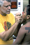 """Native American(s) @ Thunderbird powwow - father paints son face in preparation for pow wow dance contest - mother looks on - Queens, NY .... A pow-wow (also powwow or pow wow or pau wau) is a gathering of North America's Native people. The word derives from the Narragansett word powwaw, meaning """"spiritual leader""""."""