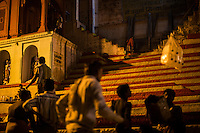 A child ascends the stairs on the banks of the river during Aarti, a prayer offered to the River Ganges and a major nightly tourist attraction, along the banks of the holy river Ganges in Varanasi, Uttar Pradesh, India on 15 November 2013. Guria runs a boat school targeting the boatmen's children, who are exposed and vulnerable to exploitation when they sell flowers and floating candles to the millions of tourists who come to Varanasi.