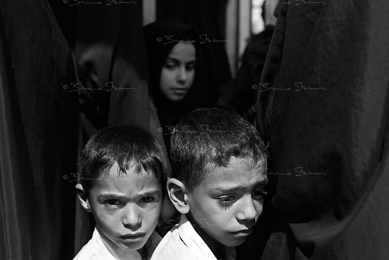 """Baghdad, Iraq, June 7, 2003.Women and children waiting for medecine and vitamine distribution at an """"ECHO"""" sponsored clinic in Hay Tareq, the most miserable slums around Baghdad. Most children suffer from chronic malnutrition and many are affected by diseases caused principally by the absence of drinking water.."""