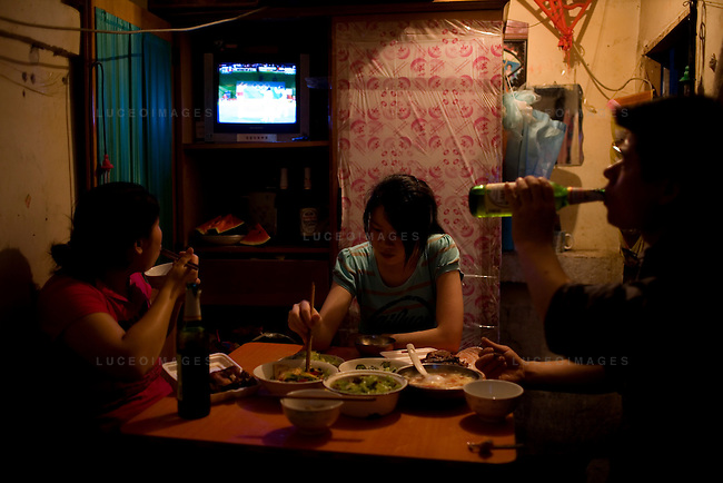 Sun Yu Bin, right, and his wife Liu Guo Min watch an Olympic Judo match with their daughter Sun Lan while eating dinner in their bedroom in a hutong in Beijing, China on Friday, August 22, 2008.  Kevin German
