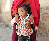 A young Tibetan girl is held by a female monk in the Amdo region of the Tibetan Plateau. Up to 100,000 nomads have been removed from the highland grasslands of the Tibetan Plateau. Climate change, mining and government policy are causing the rapid disappearance of this unique culture.