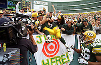 A Green Bay Packers player is swallowed up by adoring Packers fans after scoring a touchdown and executing a perfect Lambeau Leap