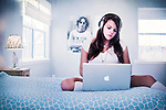 Close up of young woman with blonde hair wearing headphones sitting on bed using apple laptop computer with poster of John Lennon in background