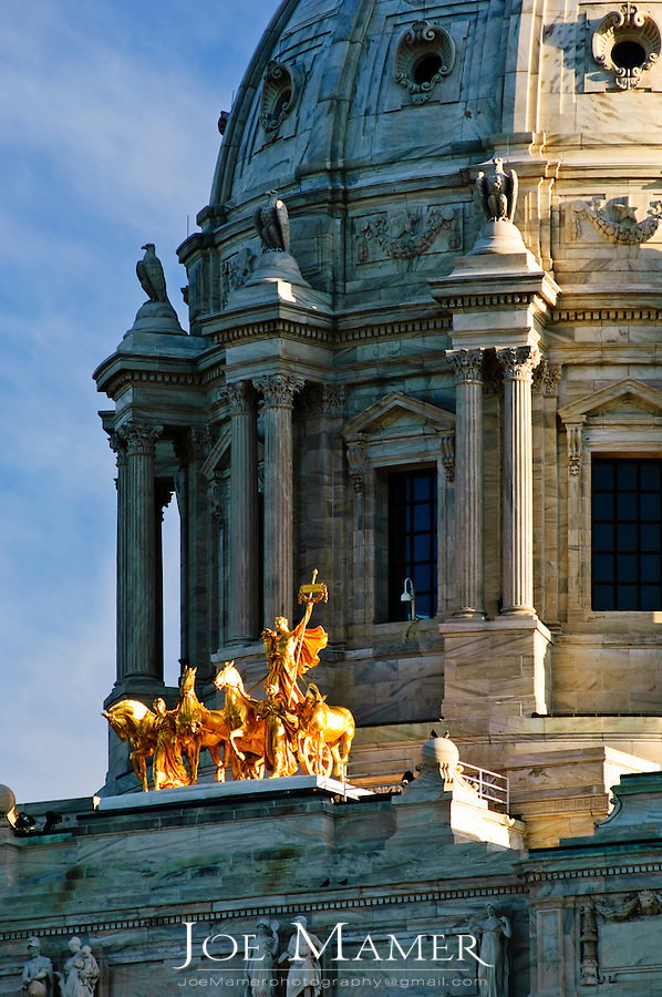Minnesota State capitol building quadriga statue. Daniel Chester French--sculptor of the Lincoln Memorial in Washington DC--designed the quadriga or golden horses on the exterior of the building. The quadriga figures are made of copper and covered with 23-1/2 karat gold leaf...Minnesota State capitol building. The building was designed by Cass Gilbert. The unsupported dome is the second largest in the world, after Saint Peter's. Work began in on the capitol in 1896, and construction was completed in 1905. It is the third building to serve this purpose: the first capitol was destroyed by fire in 1881, and the second was completed in 1883, but was considered to be too small almost immediately.