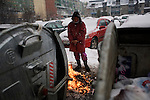 Prishtina neighborhood of Dardania. Roma woman with a fire...Large snow storms in Kosovo, 2/19/09.