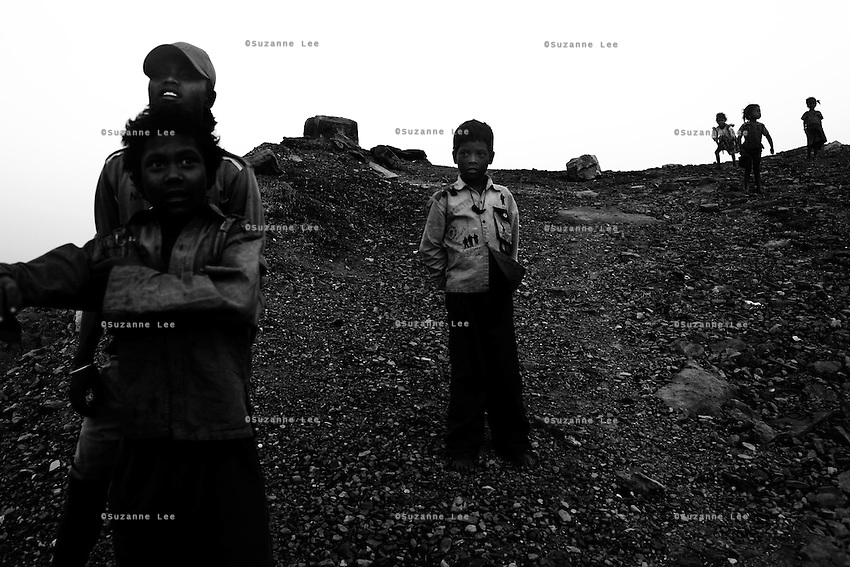 Families of coal miners live above fire in Jharia, a small town near Dhanbad, Jharkhand, India. Men, women and young children live on the perimeters of the government coal mines, stealing coal pieces to sell to the coal markets at a small profit. Efforts have been made by the government to relocate these squatter villages to nearby towns but these families would rather live above the burning mines, risking regular ground cave-ins and death by accidental falling into the holes of fire. Photo by Suzanne Lee