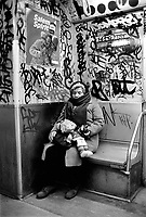 USA. New York City. Old woman asleep with a doll in the subway. Graffiti. Advertisement for Salem cigarettes. Company Campaign: Salem Shows Spirit. The R. J. Reynolds Tobacco Company (RJR) is an indirect wholly owned subsidiary of Reynolds American Inc. which in turn is 42% owned by British American Tobacco. 15.03.86 © 1986 Didier Ruef