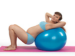 Pregnant young woman doing pilates workout with a fitness ball isolated on white background