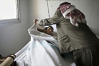The Father of Salim Ibrahim trys to make his son comfortable as he lies in the military hospital in Damascus, just a few kilometers from fighting. Salim (22) was shot in the chest in the Town of Deraa on 23rd of January. Government forces have suffered many casualties in the last few days as they try to gain back control of many areas, including suburbs of the capital. Protests against the ruling Baathist regime erupted in March 2011 and although they were peaceful government forces violently repressed them. In response to being commanded to shoot unarmed civilians large numbers of men deserted the army and formed the Free Syrian Army and an armed uprising began with major clashes taking place in early 2012.