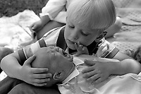 Little boy holding crying baby