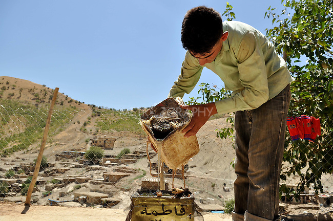 GALALA, IRAQ: Goran Abu Bakir transfers tree sap into a larger container.<br /> <br /> Bnysht, a Kurdish is chewing gum made from the sap of the Daraban tree.  The sap is only harvested during July and August for 6 weeks using clay cups to catch the liquid as it is drawn for the tree's bark.<br /> <br /> Photo by Aram Karim