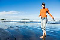 Girl running from approaching tide, New Zealand