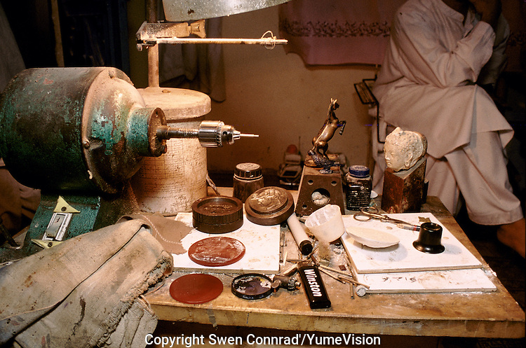 An Afghan forger desk, working on a new coin of Alexander the great for the English market. Peshawar, Pakistan..On the right, a head of Buddha from the National museum of Kabul Afghanistan, will be copy and sale to the foreign as original for five to height hundred dollars.