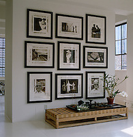 A low wooden bench acts as a sidetable beneath a collection of black and white photographs