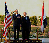 Baghdad, Iraq - December 14, 2008 -- United States President George W. Bush, left, and President Jalal Talabani of Iraq stand between the United States and Iraq flags, Sunday, December 14, 2008 during the playing of the U.S. national anthem. Bush is on his final visit to Iraq before the end of his second presidential term to meet with Iraqi leaders and sign a ceremonial copy of the security agreement. .Credit: Kristin Fitzsimmons - U.S. Navy via CNP