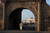 ESSAOUIRA, MOROCCO - MAY 10 : A low angle view of the Porte de la Marine on May 10, 2009 in Essaouira, Morocco. A man in traditional dress walks through the arch of the Porte de la Marine, built in 1771,  towards the boats. In the background the Ramparts and the Medina are lit by the evening sun. Essaouira, on the windswept Atlantic coast, was re-built in the 18th century by French architect Theodore Cornut to the orders of Sultan Ben Abdullah. Surrounded by ramparts it is now becoming more popular with tourists. (Photo by Manuel Cohen)