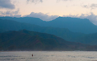 A surfer just off Hanalei Beach Park on the North Shore of Kauai at sunset admiring the blue-tinged mountains receding to the formidable cliffs of Na Pali.