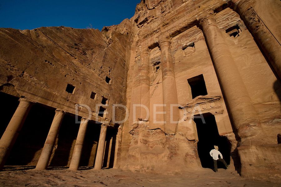A male tourist wearing a hat stands in the entrance to the Um Tomb in the Nabatean ancient city of Petra, Jordan.