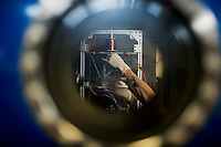 A researcher adjusts a small satellite as it levitates in a vacuum chamber used to test thruster design in the Space Propulsion Lab at MIT.  Paulo Lozano is the Associate Director of the Space Propulsion Lab and an Associate Professor of Aeronautics and Astronautics at MIT in Cambridge, Massachusetts, USA.  Lozano's current research focuses on the development of small thrusters for satellites.  The thrusters his lab has developed are about the size of a single die cube and contain enough fuel to power the thrusters for a year in space.  The thrusters will be used on small satellites.