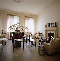 A collection of orchids in full bloom cover a table in this drawing room which is furnished with a selection of antique Chinese chairs, benches and tables
