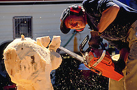 Chainsaw sculpture - Sculptor creating art with his chain saw while he wears ear protection.