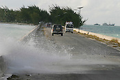 The waves from a 'king tide' crash over the man made causeway on the island of Kiribati. The islands, and their way of life, are endangered by rising sea water levels which are eroding the fragile atoll, home to approximately 92,000 people.